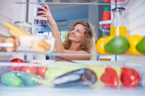 Frau, die Lebensmittel aus dem Kühlschrank voller Lebensmittel nimmt. – Foto