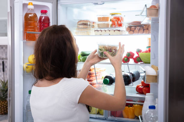 Woman Taking Food From Refrigerator stock photo