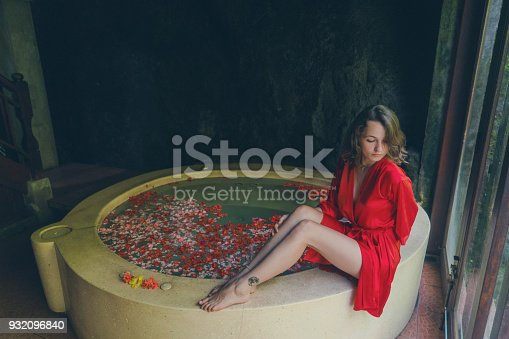 610769340istockphoto Woman taking hot tub with flower petals 932096840