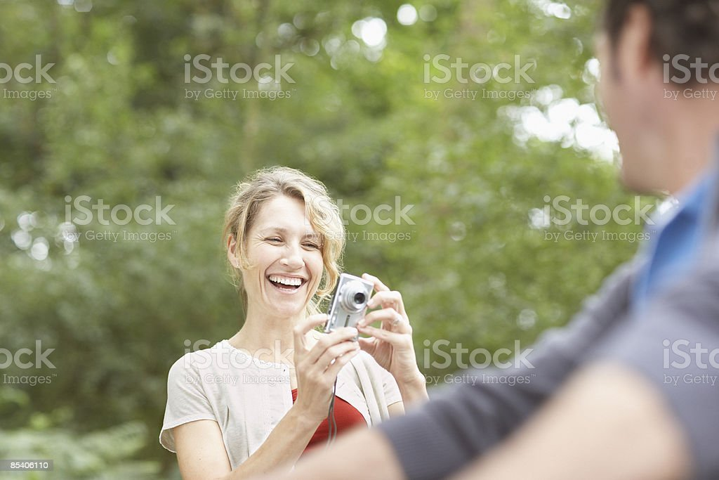 Woman taking husbands picture outdoors royalty-free stock photo