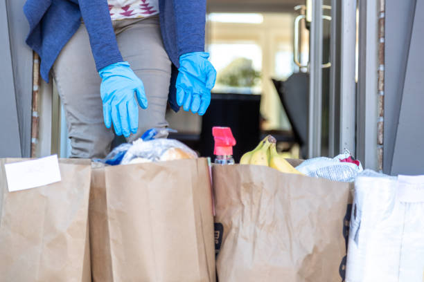 Woman taking in Grocery bags waiting outside at front door after delivery stock photo