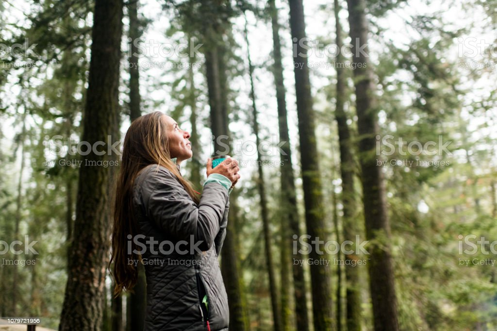 Woman taking in the beauty of nature with a cup of coffee royalty-free stock photo