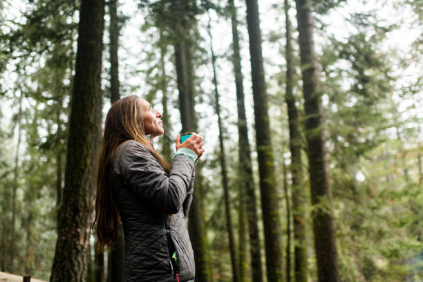 Woman taking in the beauty of nature with a cup of coffee stock photo