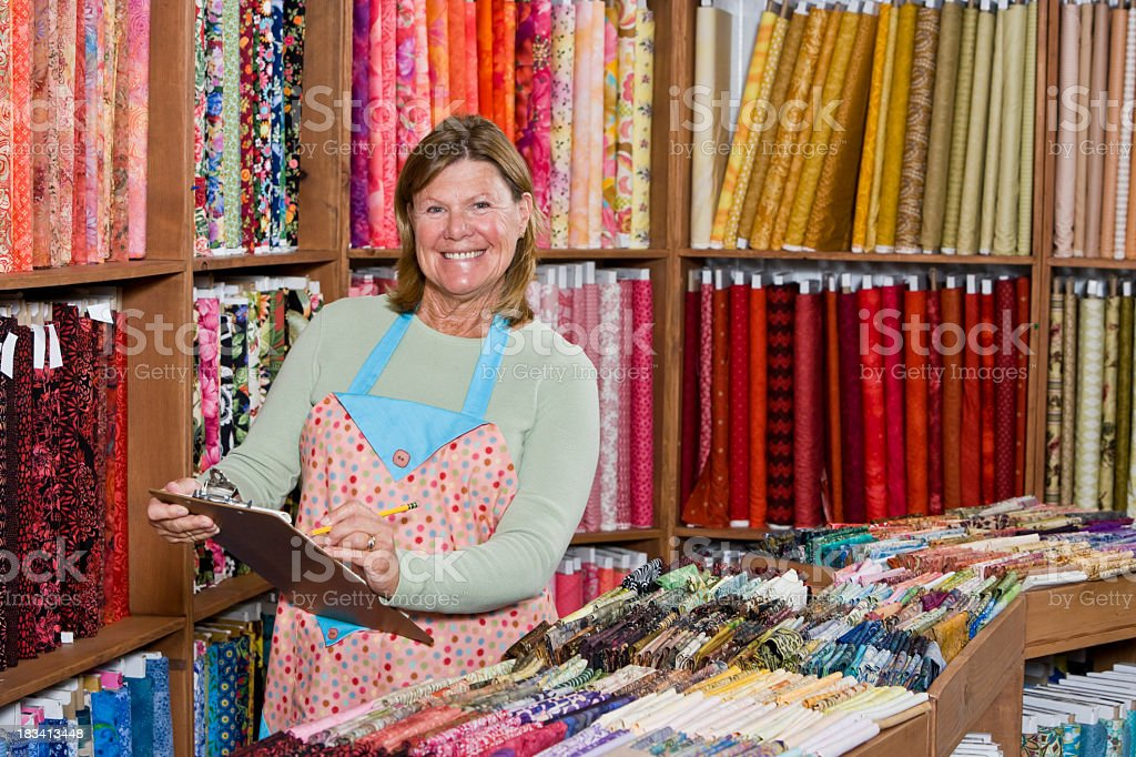 Woman taking inventory in fabric shop royalty-free stock photo