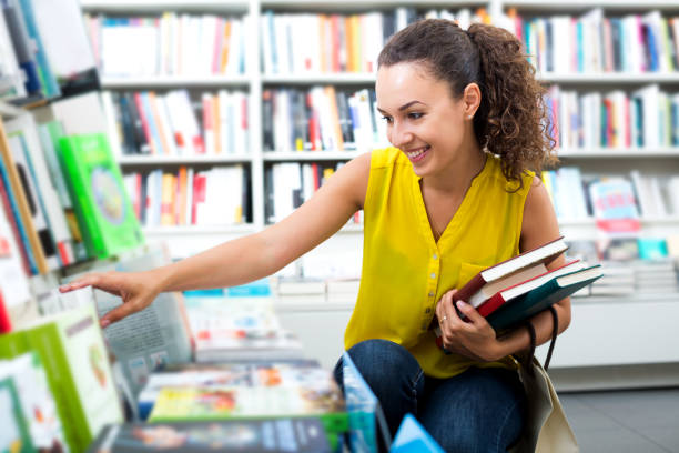 Woman taking literature books in store stock photo
