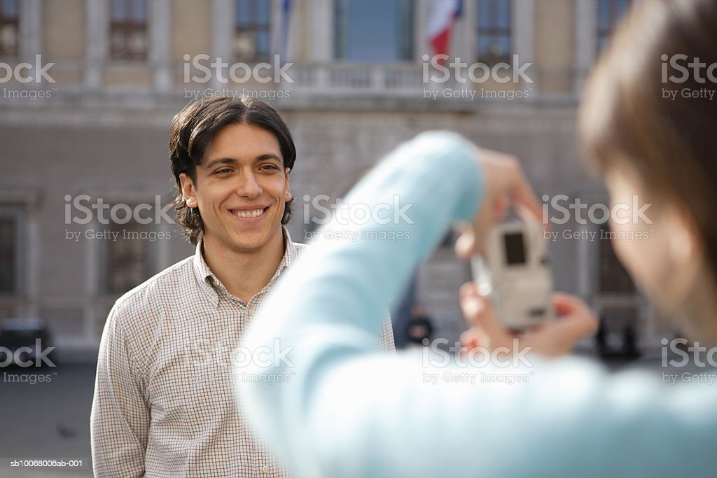 Woman taking man's picture on street royalty-free stock photo