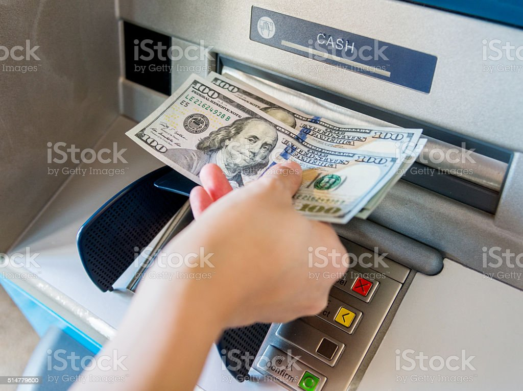 Woman taking money out of the ATM stock photo