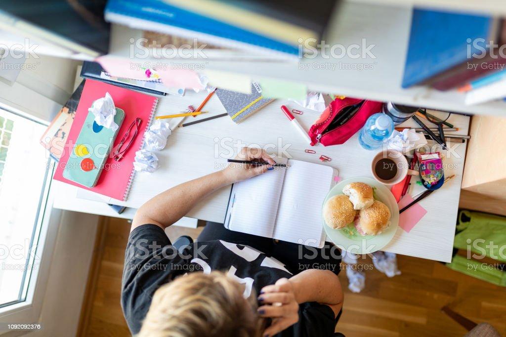 Woman taking notes messy desk, talking on the phone - fotografia de stock
