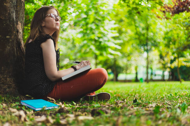 Woman taking notes while making research from a book outdoors stock photo