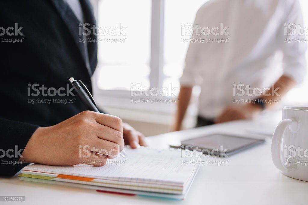 Woman taking notes with male colleague in background stock photo