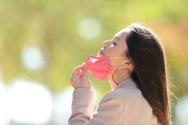 Woman taking off mask breathing fresh air in a park stock photo