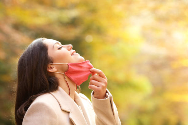 Woman taking off mask breathing fresh air in autumn stock photo