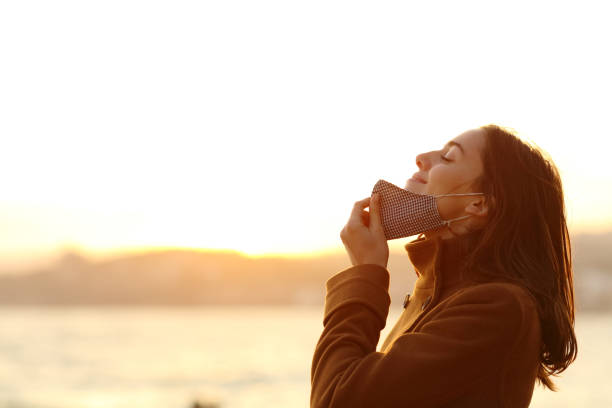 Woman taking off mask to breath fresh air on the beach stock photo