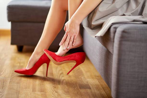 Woman taking off red high heels shoes after work and massages feet at home on gray couch.
