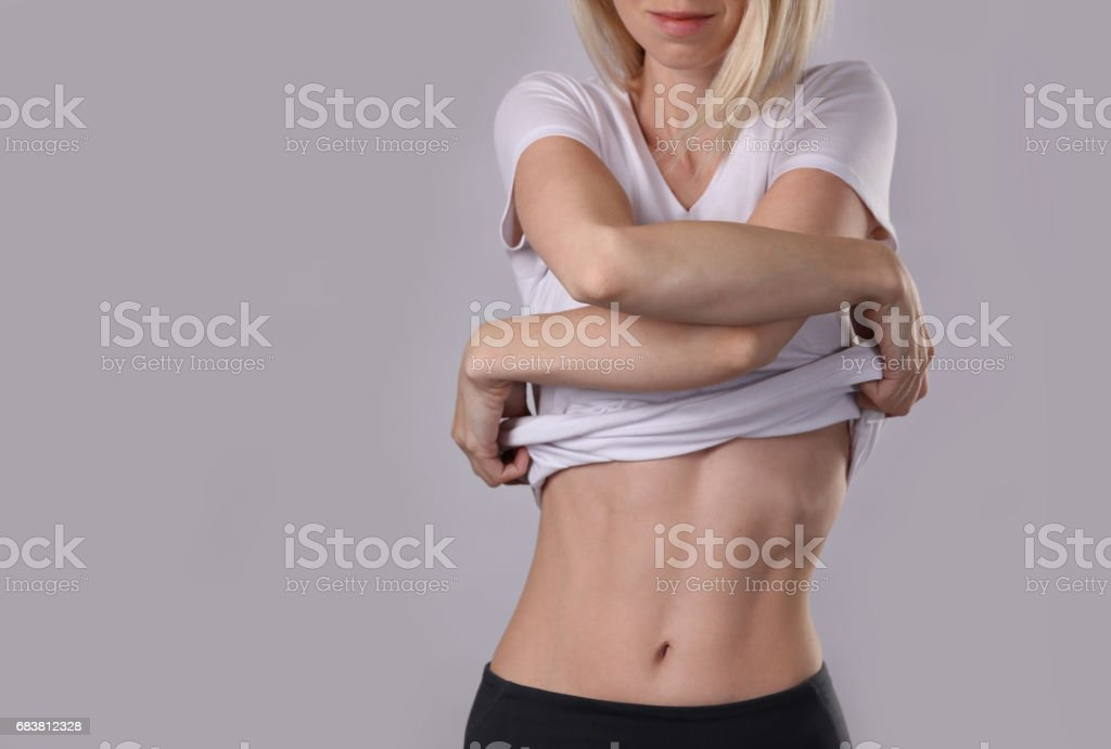 Woman taking off white t-shirt . Healthy, shape female body,, waist, perfect abdomen muscles. Sport, fitness, Dieting results, active lifestyle concept stock photo