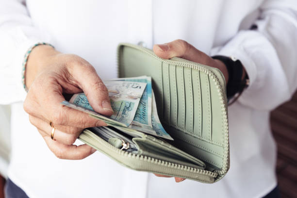 Woman taking out pounds from her pocket wallet Close up of hand of woman taking out pounds from her purse wallet money stock pictures, royalty-free photos & images