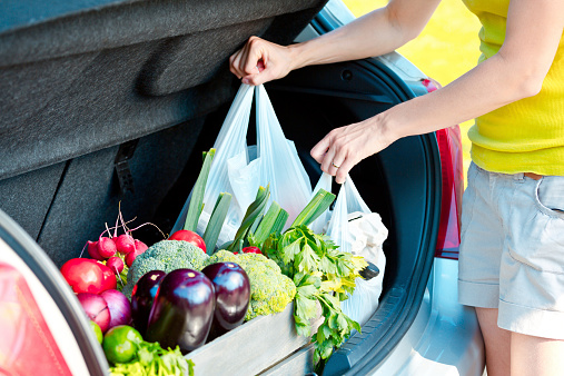 Woman Taking Out Shopping Bags From Car Trunk Stock Photo - Download Image Now