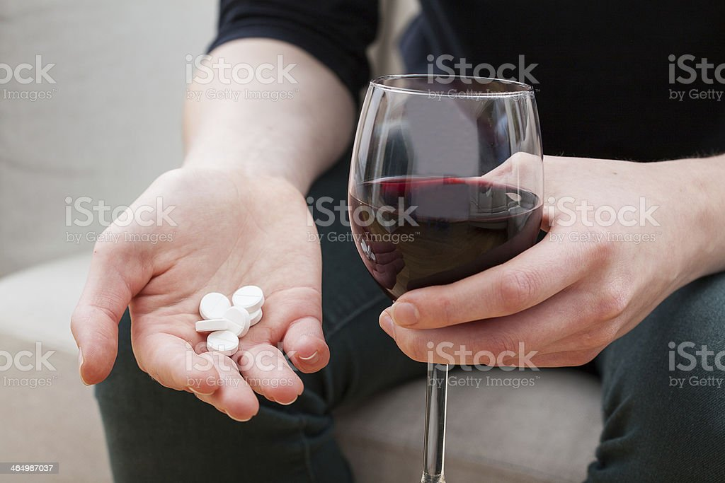 Woman taking painkillers and alcohol stock photo
