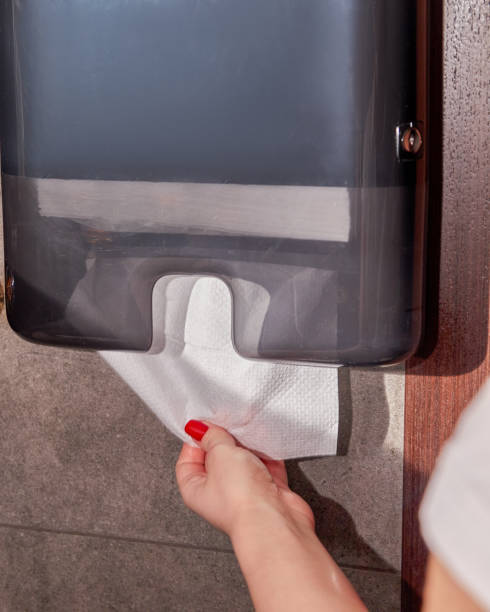 Woman taking paper towel for drying hands. stock photo