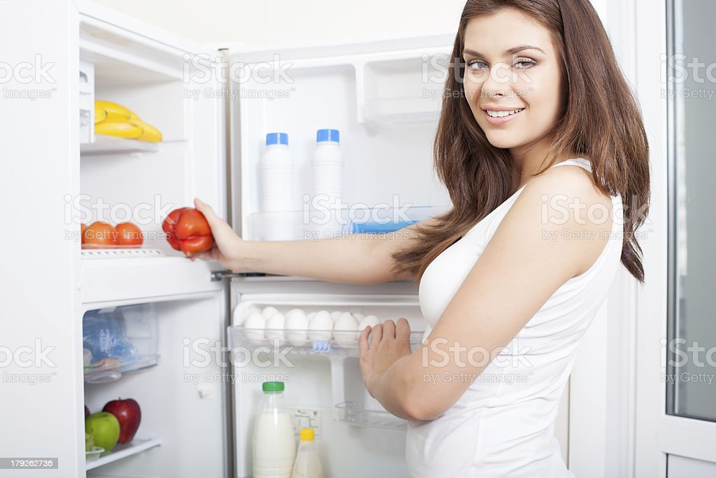 Woman taking pepper from fridge royalty-free stock photo