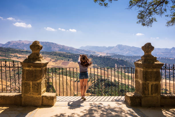 Woman taking photo from the mountaintop in Alameda del Tajo park in Ronda, Spain stock photo