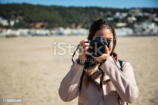 Woman taking photo front view with DSLR camera