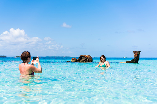 Woman taking photo of another woman in turquoise sea near Isla de  Perro island in Caribbean See