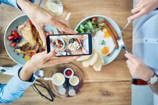 Woman taking photo of breakfast served in cafe