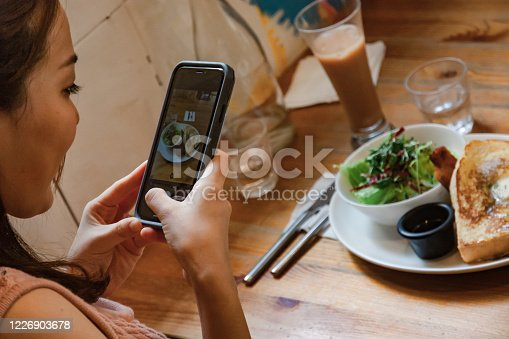 Woman taking photo of burnch with smartphone