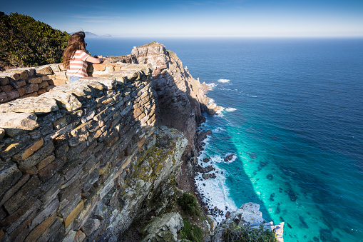 Woman taking photo of cliffs at Cape Point, South Africa