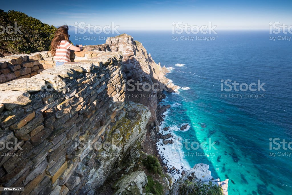 Woman taking photo of cliffs at Cape Point, South Africa stock photo