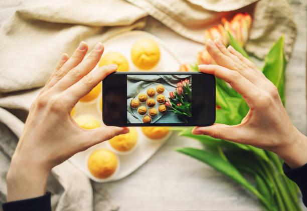 Frau fotografiert Cupcakes mit Smartphone – Foto