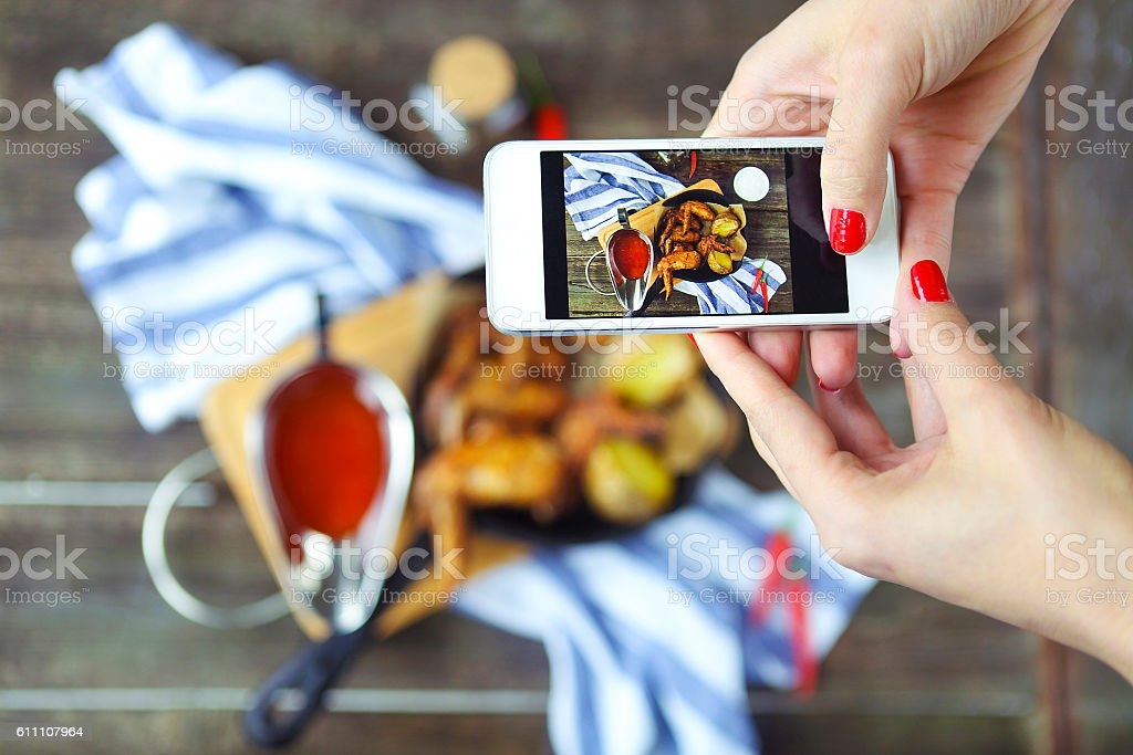 Woman taking photo of hot meat dishes on wooden background stock photo