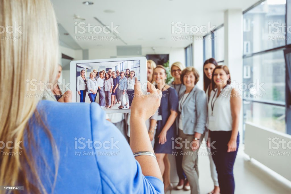 Woman taking photo of large group of happy women, using digital tablet Woman taking photo of large group of happy women, using digital tablet. Active Seniors Stock Photo