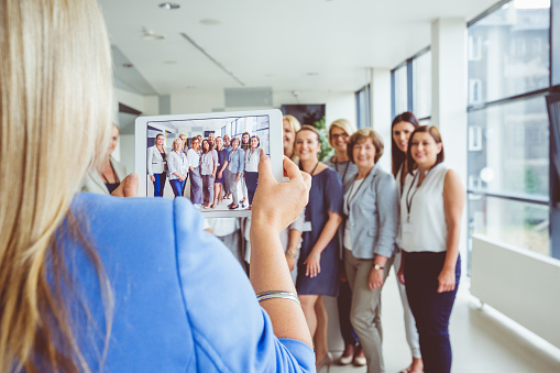 Woman Taking Photo Of Large Group Of Happy Women Using Digital Tablet Stock Photo - Download Image Now