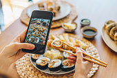 Woman taking photo of a sushi plate with smartphone