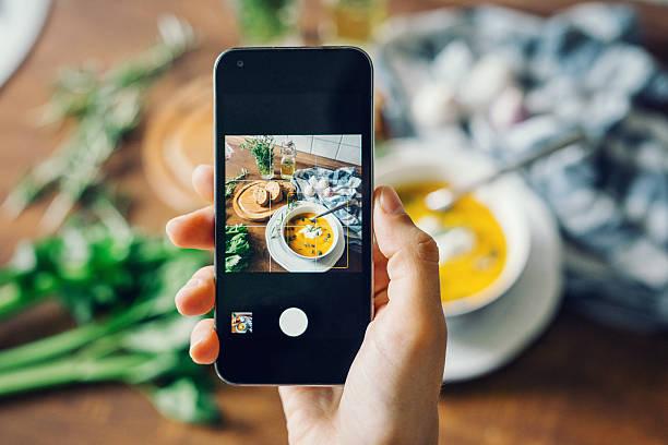 frau macht foto von kürbissuppe mit smartphone - fotohandy stock-fotos und bilder