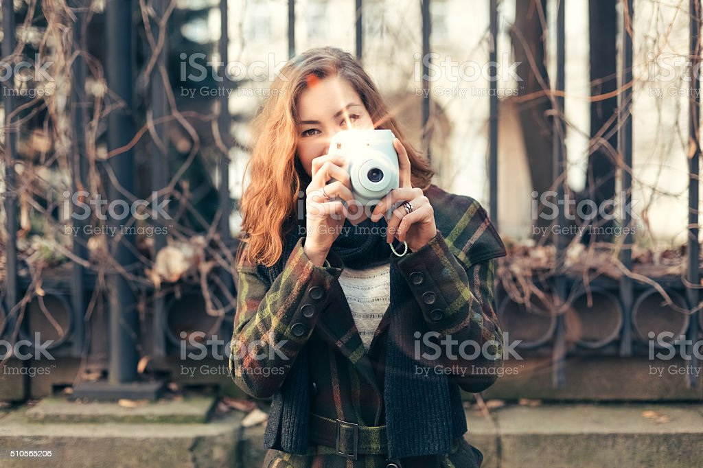 Woman taking photo with instant camera stock photo