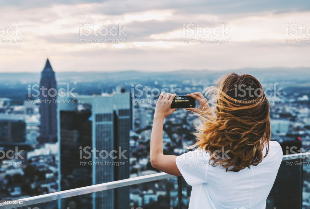 Woman taking photo with mobile phone above city stock photo