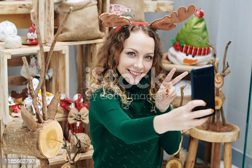 Portrait of young smiling curly woman taking photos among Christmas decorations