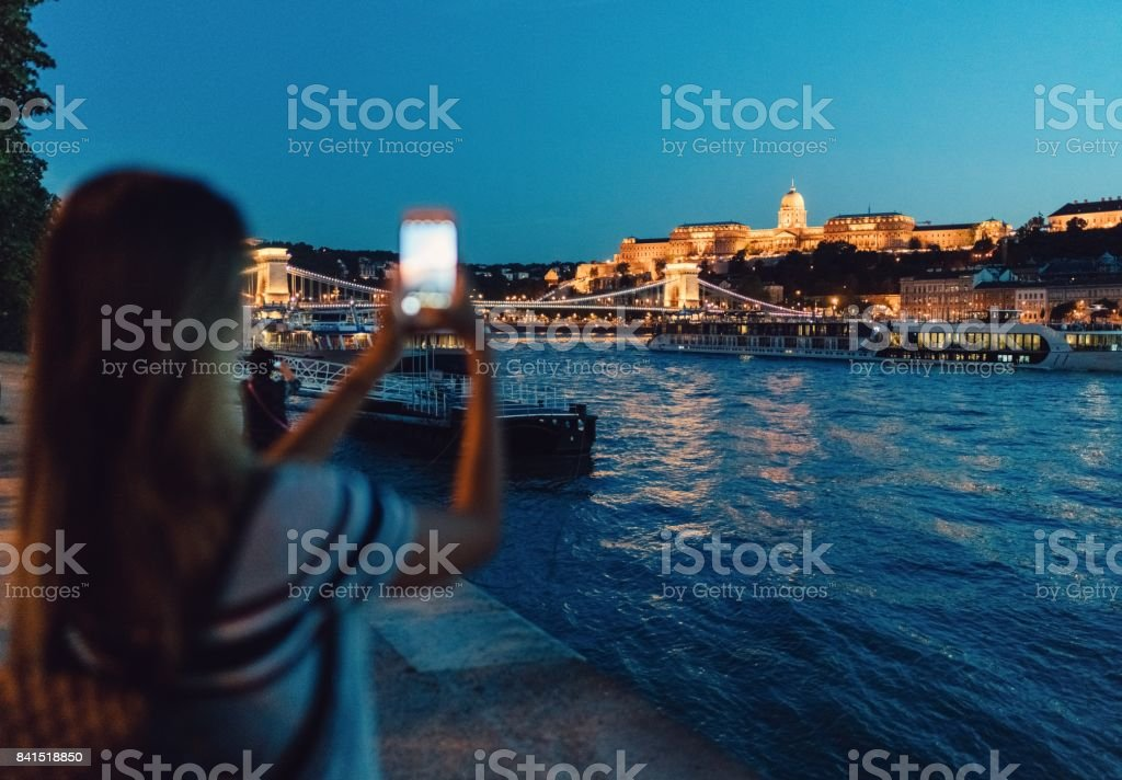 Woman taking photos of Budapest city at night stock photo