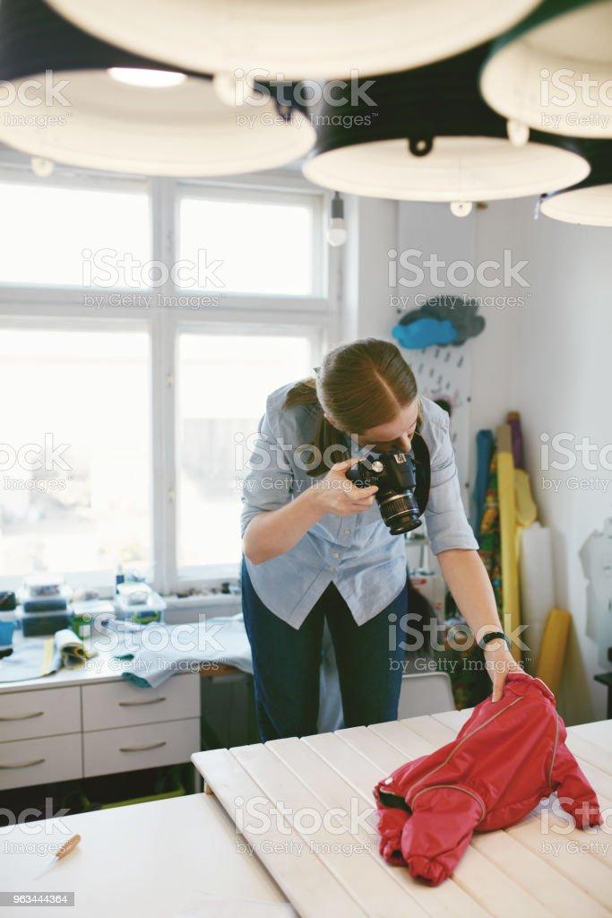 Woman Taking Photos Of Dog Clothes In Clothing Atelier - Zbiór zdjęć royalty-free (Biznes)