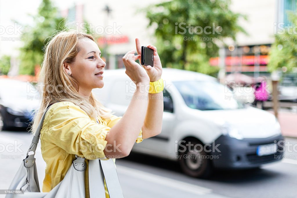 Woman taking photos with mobile phone on the street royalty-free stock photo
