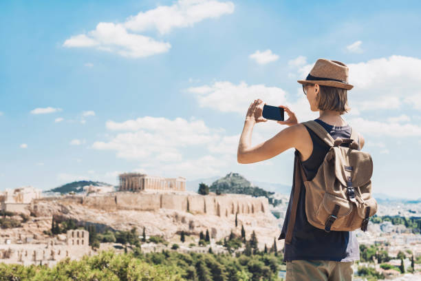 Woman taking photos with smartphone on vacations in Athens stock photo