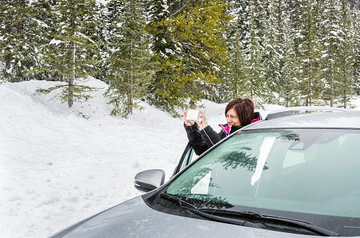 Woman Taking Picture after Stopping her Car on a Mountain Road