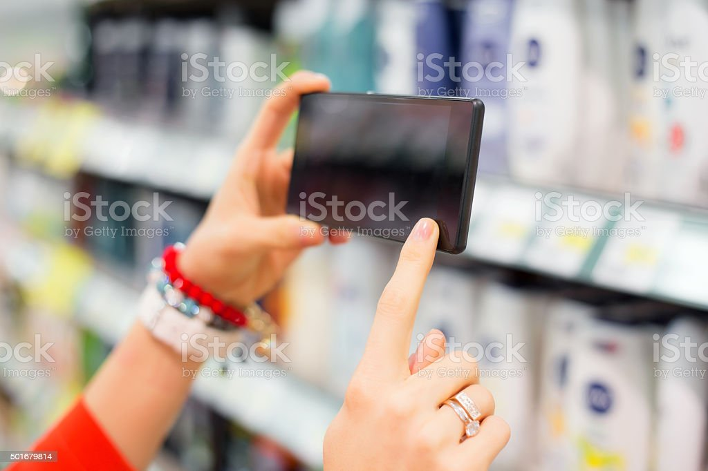 Woman taking picture in supermarket stock photo