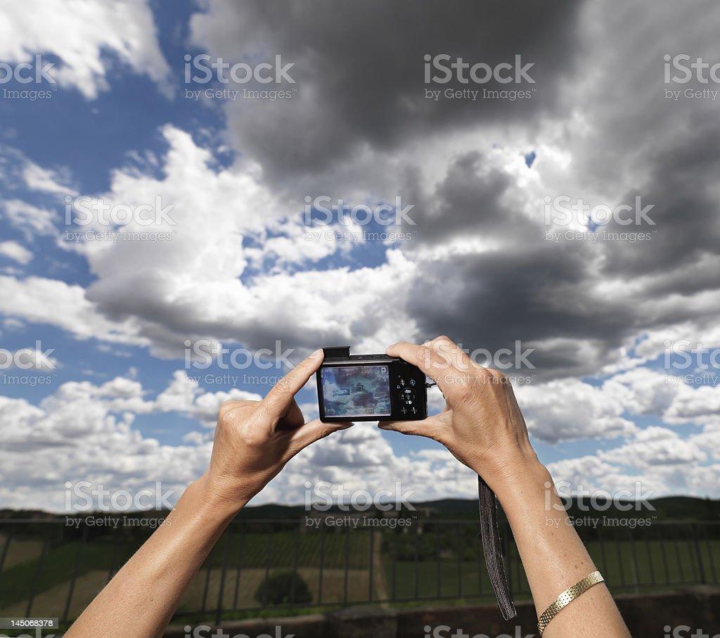 Woman taking picture of cloudy sky stock photo