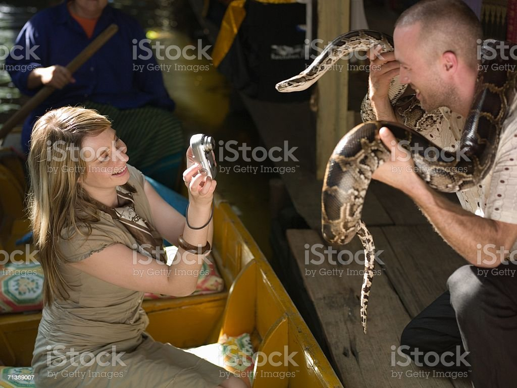Woman taking picture of man holding snake royalty-free stock photo