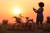 Silhouette of beautiful african woman with bike using smart phone, in nature.