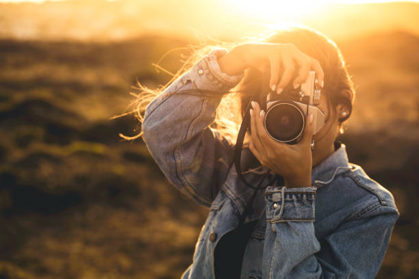 Woman Taking Picture Outdoors Beautiful woman taking picture outdoors with a analog camera photografi stock pictures, royalty-free photos & images